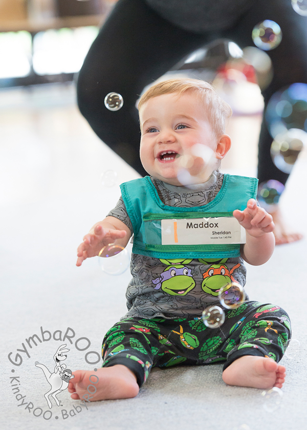 A baby having developed good muscle tone sitting on the mat at BabyROO GymbaROO mat time loving the bubbles.