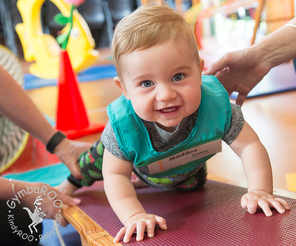 A happy baby crawling on the Gymbaroo equipment and developing strength at Gymbaroo Babyroo